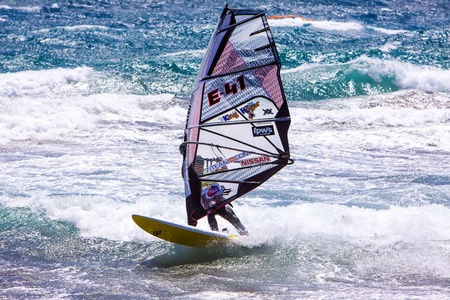 competes: POZO IZQUIERDO, CANARY ISLANDS, GRAN CANARIA - JUL  11  A professional windsurfer competes at the International PWA Competition on JUL  09, 2011 in Pozo Izquierdo beach, Gran Canaria  This event is under PWA rules
