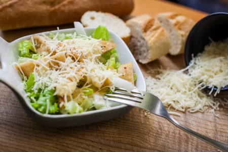 fresh caesar salad on bowl with parmesan cheese photo
