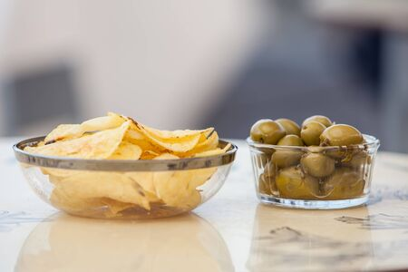 flavoured: potato chips and olives on a glass bowl