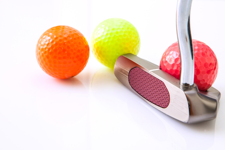 putter: Golf putt and yellow ball in white background