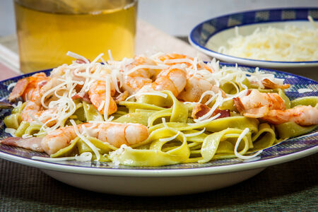 pasta tagliatelle with prawn and bacon on the wooden table photo
