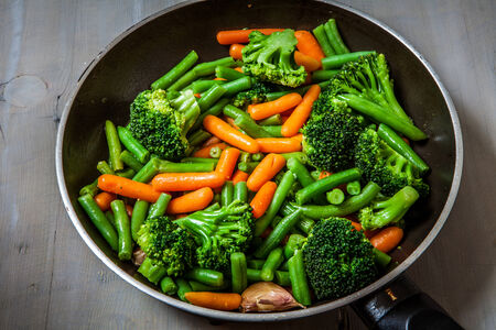 healthy vegetables cooked on a pan on a wooden table
