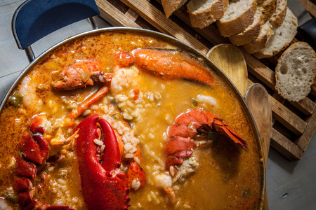 spanish food: traditional seafood rice with lobster and tomato sauce
