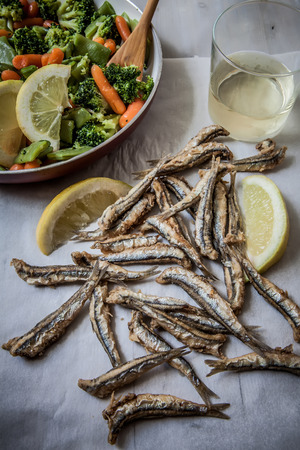 anchovy fish: a few deep fried anchovies with lemon and vegetables