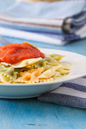 a white bowl with farfalle and tomato sauce on table photo