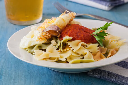 a white bowl with farfalle and tomato sauce and deep fried egg photo