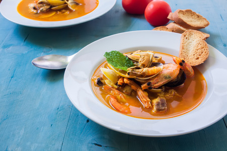 seafood soup: a white bowl with seafood soup with fish