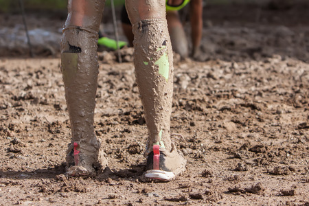 mud woman: woman legs with dirty socks with mud on extreme run