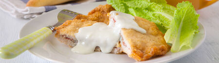 cordon: french deep fried cordon bleu with salad on white plate