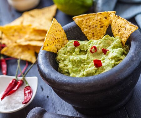 black stone bowl with fresh guacamole and nachos for dip