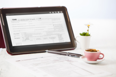 preparing 1040 tax form with a cup of coffe and a tablet photo