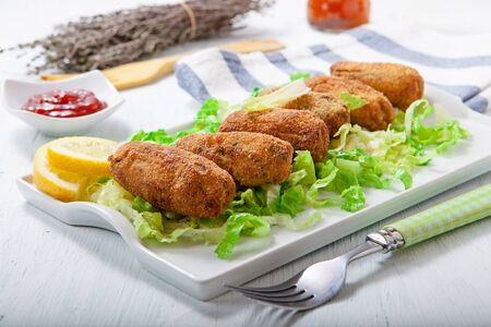 croquettes: homemade chicken and vegetables croquettes on white tray