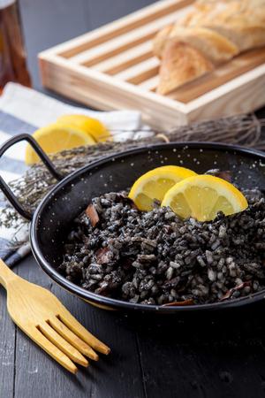 Risotto de mariscos con calamares tinta negro en pote Foto de archivo - 40194514