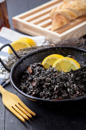 black octopus: seafood risotto with black calamari ink on pot
