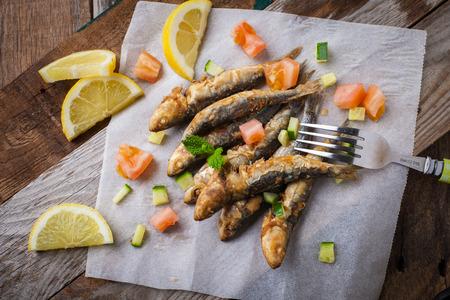 plato de pescado: sardinas fritas con limón y ensalada en papel blanco Foto de archivo