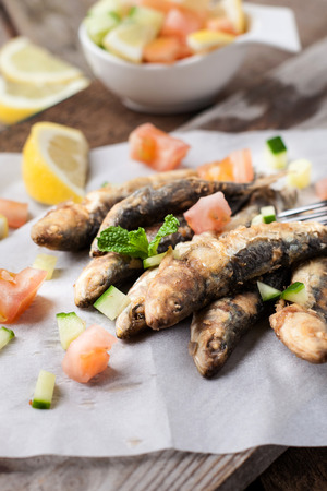 seafish: deep fried sardines with lemon and salad on white paper