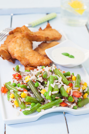 chicken fingers: rice and vegetables salad with chicken fingers selective focus on rice