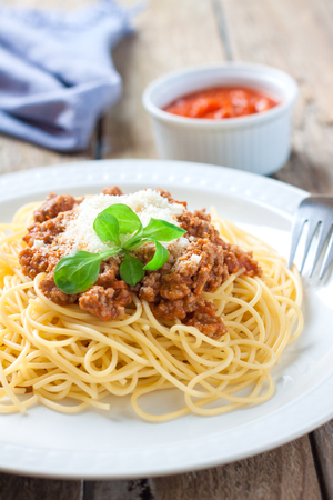 spaghetti dinner: italian pasta spaghetti with meat and tomato sauce on white plate