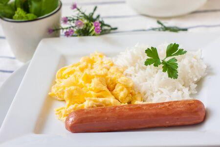 scrambled eggs: desayuno continental con huevos revueltos salchichas y arroz hervido