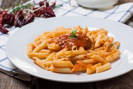 pasta: macaroni pasta with hot chili tomato sauce and basil Stock Photo