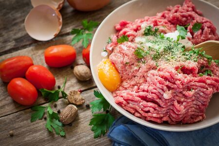 pickled: preparing beef steak tartare on bowl with egg