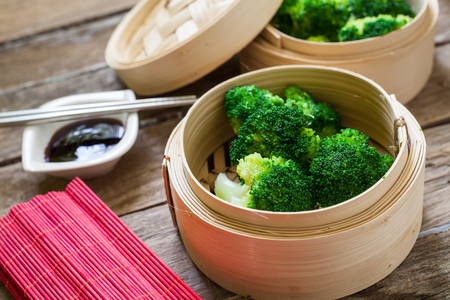 a portion: steamed fresh broccoli on bamboo pan with soya sauce for dip