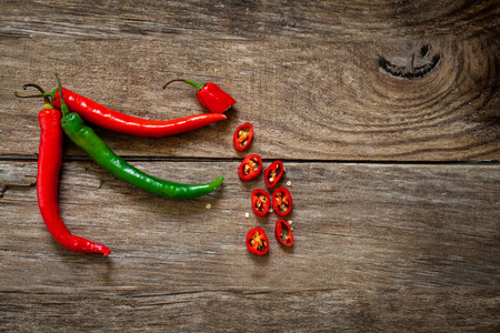spicy cooking: red and green hot chili pepper on wood board Stock Photo