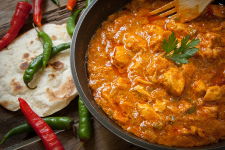 tandoori chicken: butter chicken curry on pot with green and red chili pepper