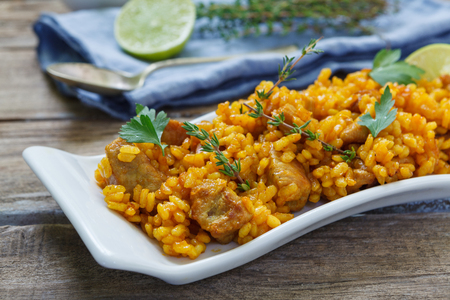 valencia orange: traditional spanish paella rice with chichen and meat on pan