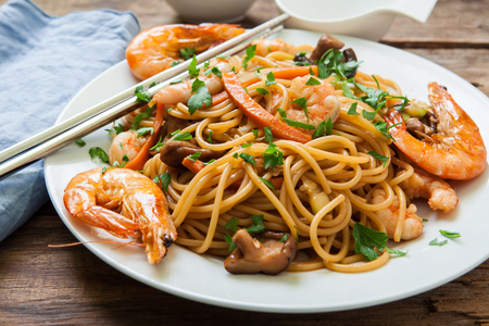 thai noodles with vegetables and prawns on plate