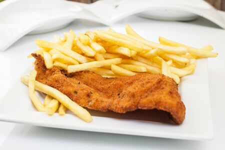 Deep fried chicken finger with lemon and fries