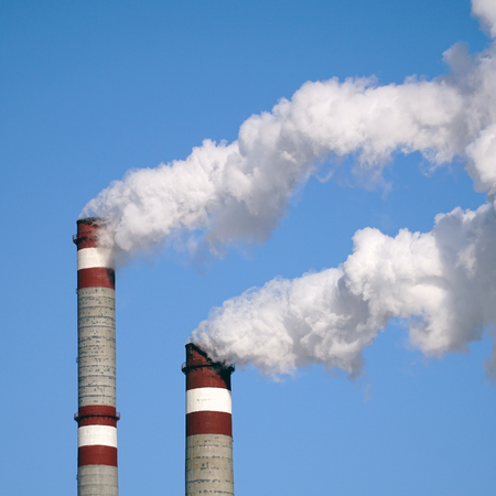 dirty environment: the industrial chimneys emits toxic pollutants into the sky polluting the environment