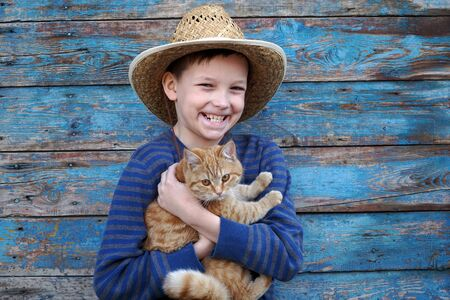 auburn: boy playing with a auburn cat outdoors Stock Photo