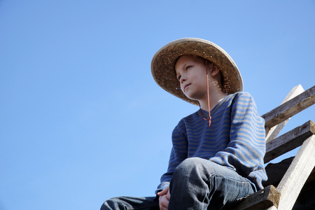 blind child: boy with hat looks into the distance.
