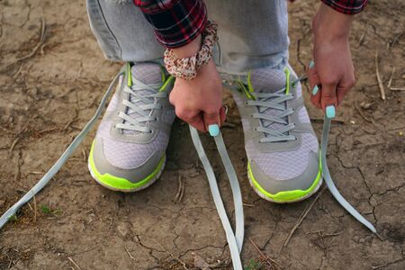 commits: young girl commits an outdoor walk and stopped to tie his shoelaces on sneakers.