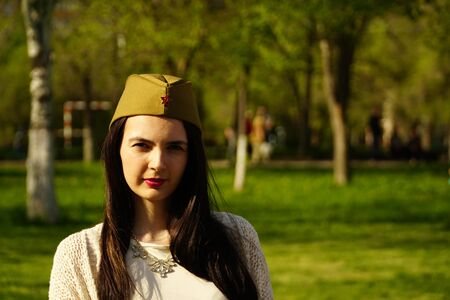 a woman wears Soviet military hat outdoors.