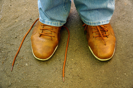 commits: men commits an outdoor walk and stopped to tie his shoelaces on sneakers.
