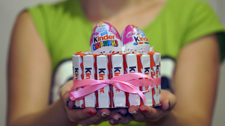 kinder: Samara, Russia - September 30, 2016: Kinder Chocolate is one of the popular childrens confection. Young mother cooked cake from Kinder Surprise, daughters birthday. Editorial