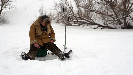 Fisherman catches a fish on ice fishing. Stock Photo