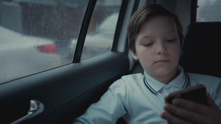 Sad, unhappy young boy riding in car through city during rainy day, using social network on his smartphone