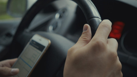 young man using map app on his smartphone in a car