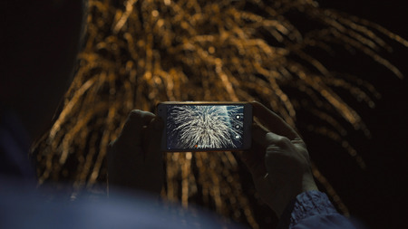 Silhouette of a man photographing fireworks at night sky. Beautiful salute in honor of the holiday. Stockfoto