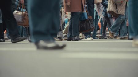 People pedestrians walks across a busy city street Stockfoto