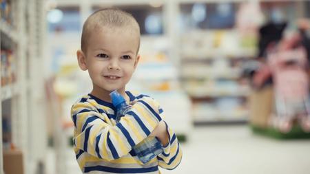 Little boy in the supermarket choose a bottle of mineral water.