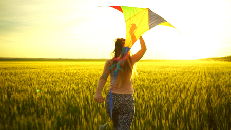 girl running around with a kite on the field. Freedom concept Stockfoto
