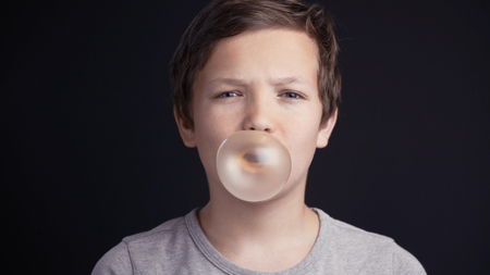 boy make bubble with chew on dark background