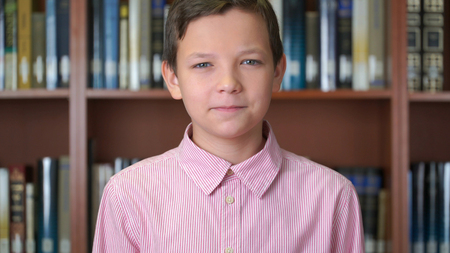 portrait shot of the cute schoolboy standing near the bookshelf in the library.