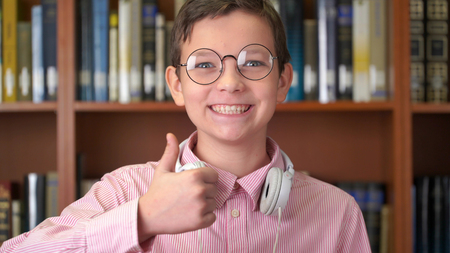 portrait shot of the cute schoolboy standing near the bookshelf in the library and doing thumb up.