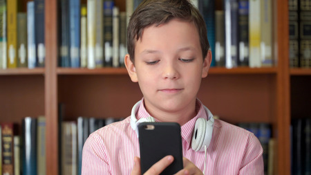 portrait shot of the cute schoolboy with smartphone standing near the bookshelf in the library.