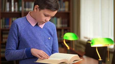 portrait shot of the cute schoolboy and standing near the bookshelf in the library and reading a book.